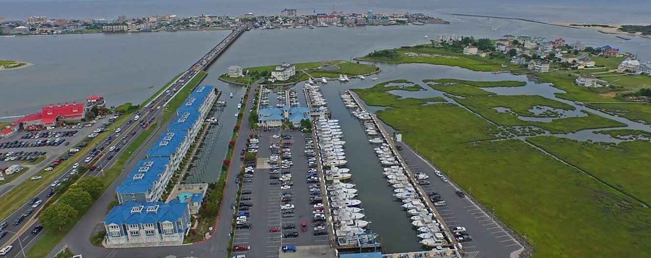 A high up view of a boat bay next to a highway and parking lot