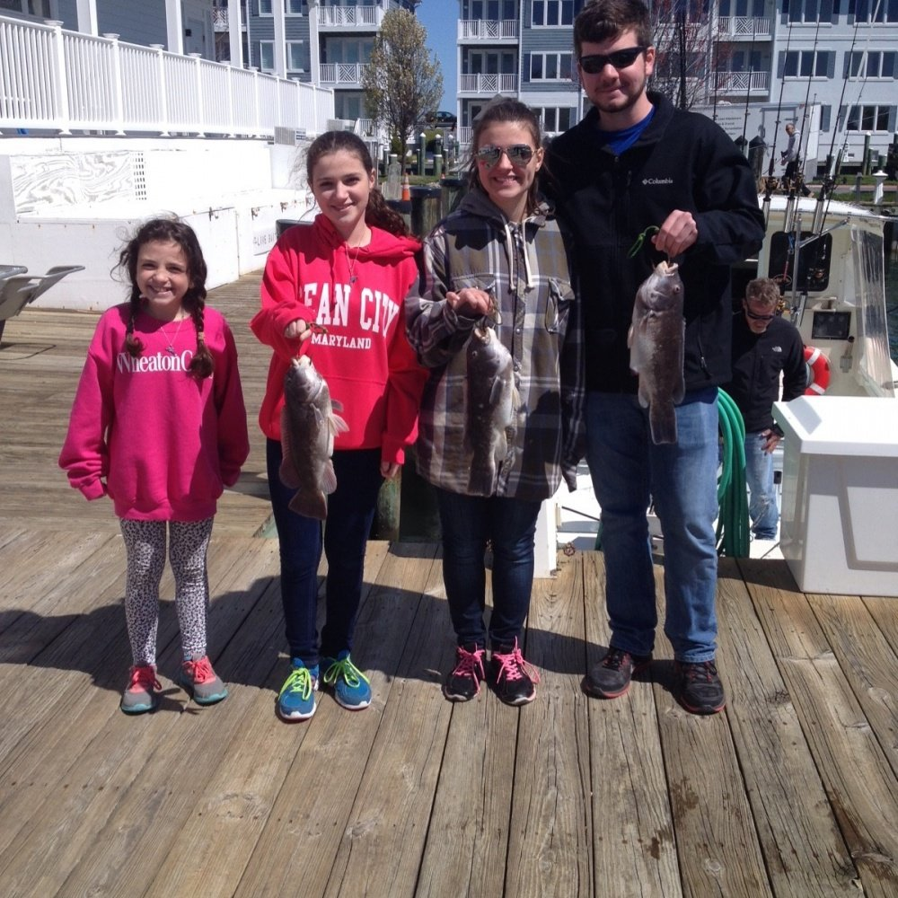 Two parents and their daughters holding up fish that they caught